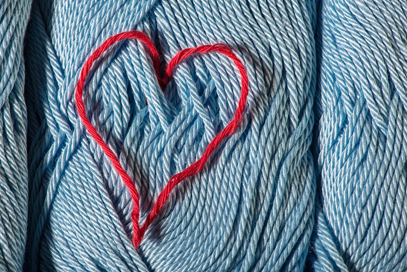 Knitted red heart on blue balls of yarn. photo