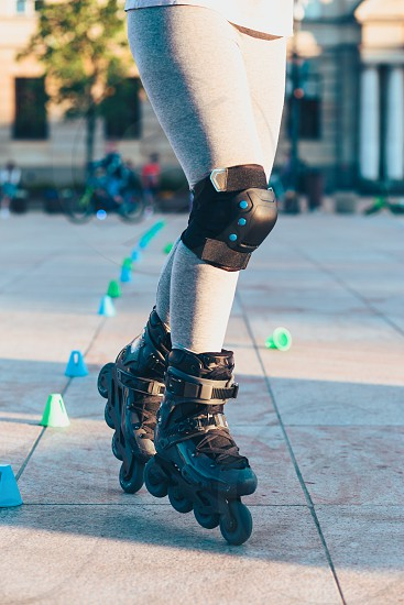 Young girl training the riding on roller skates. Closeup of female legs with roller skates and protectors photo