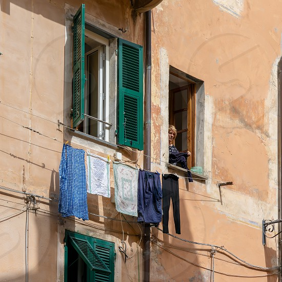 MONTEROSSO LIGURIA/ITALY  - APRIL 22 : Woman hanging out the washing in Monterosso Liguria Italy on April 22 2019. Unidentified person photo