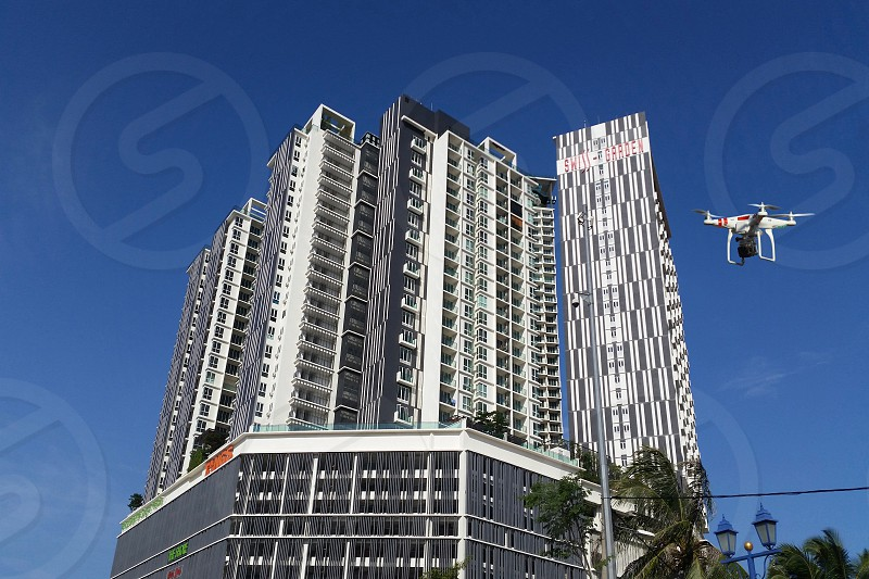 high rise building and a white quadcopter drone flying low angle photo photo