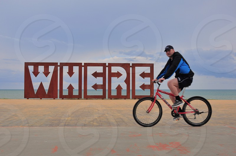 man riding bike past sign that says where photo