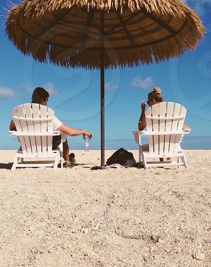 man and woman sitting on white beach chair with umbrella photo