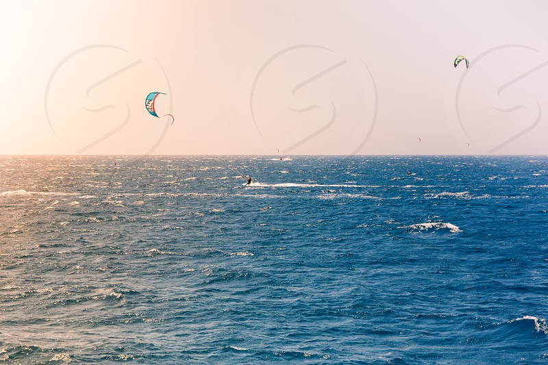 Windsurfers sailing in the Red Sea.Near the beach of Eilat Israel.Bright orange light coming from the sun on the left. photo