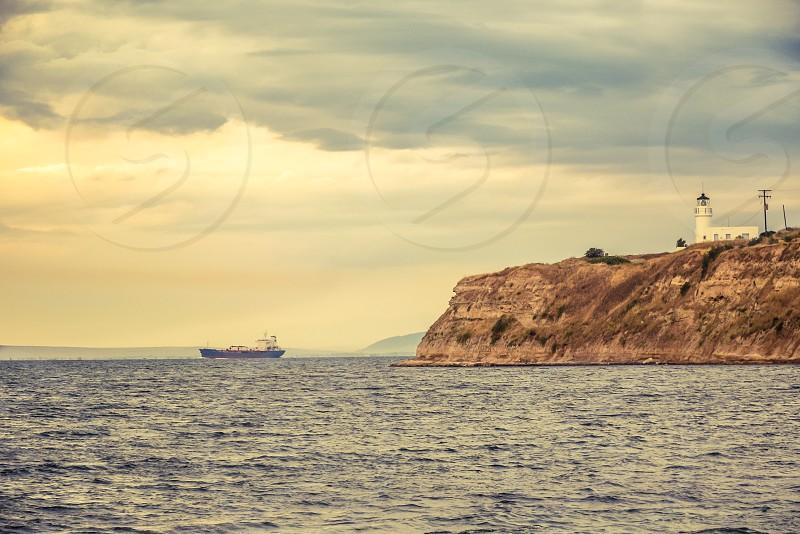 Ship And Lighthouse At Sunset Landscape photo