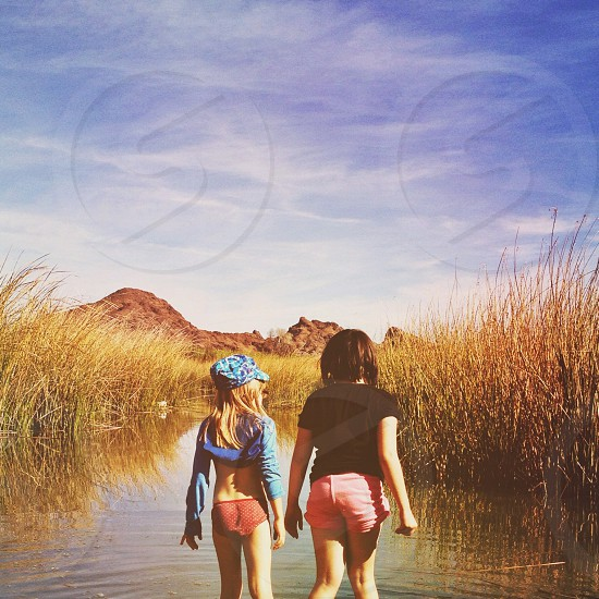 two women standing at water view photo