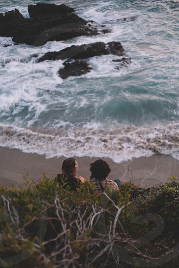 woman in black shirt and man in brown and gray button up shirt sitting on beach shore near blue ocean waves during daytime photo