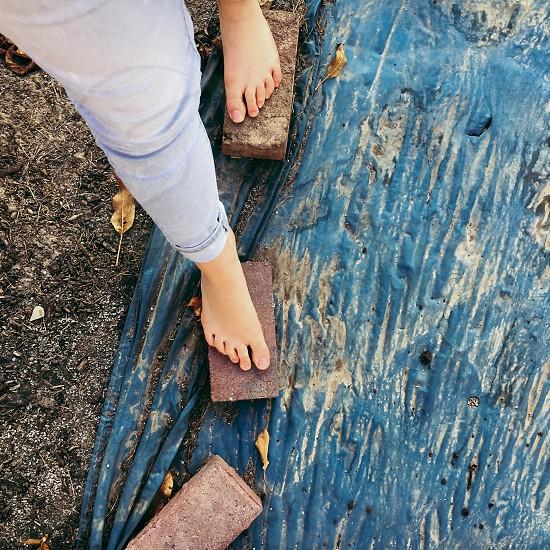Feet bricks blue dirt gravel sand stepping nature outside cold photo