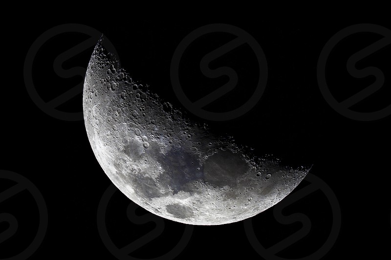 A crescent moon showing lunar craters and the terminator. High quality image taken through telescope. photo