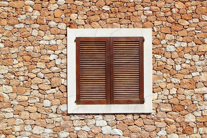 brown wooden window in masonry wall balearic islands photo