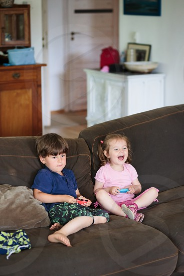 Concentrated toddlers boy and girl playing video game sitting on sofa at home photo