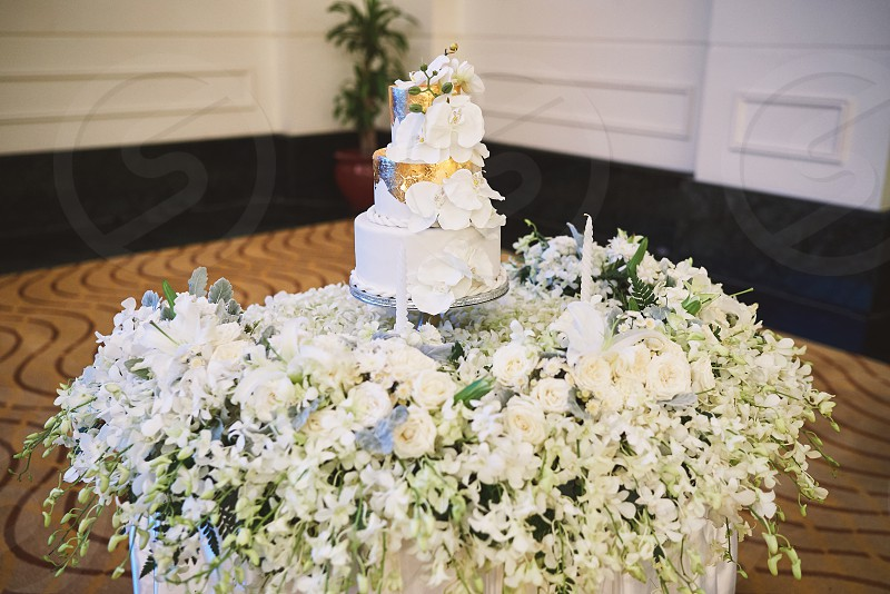Wedding cake white with gold color decoration and a bunch of white flower petals on the table photo