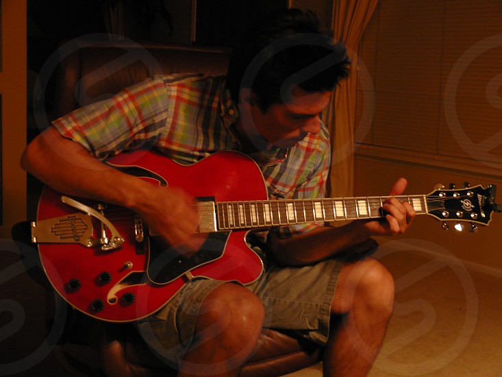 man playing red electric guitar photo