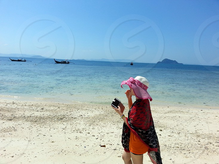 woman in white and pink bow accent floppy hat and black white dotted scarf walking on a seashore near 2 boats in the sea during daytime photo