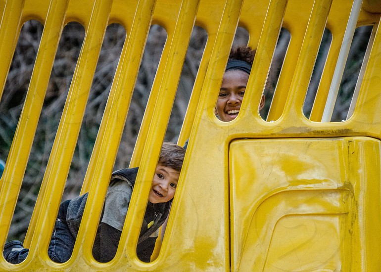 woman and a girl peaking on yellow container photo