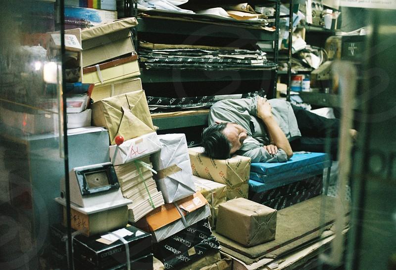 Man sleeping in an old paper shop. - Sheung Wan Hong Kong photo