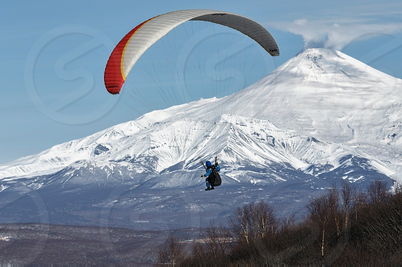 KAMCHATKA PENINSULA RUSSIA - NOVEMBER 21 2014: Paraglider flying on the background of the active Avachinsky Volcano (Avacha Volcano) on a sunny day. photo