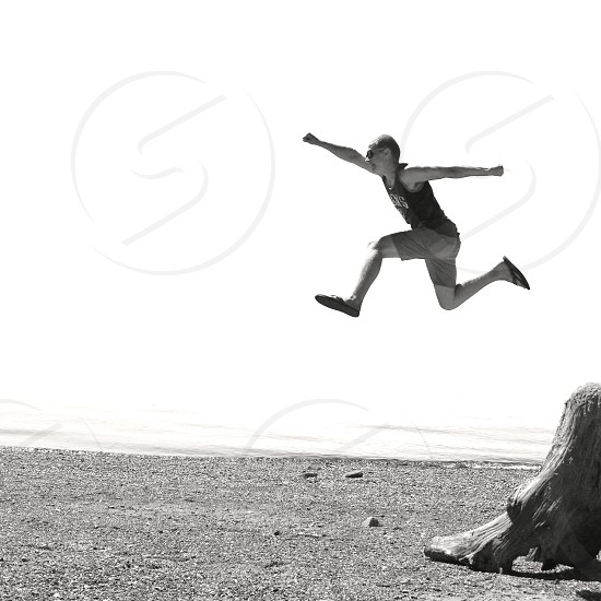 figure in black tank top jumping up arms raised on beach photo