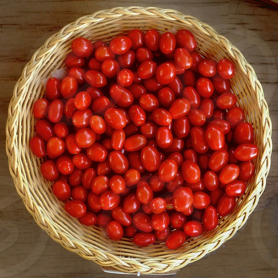 Freshly picked cherry tomatoes in a wicker basket. photo