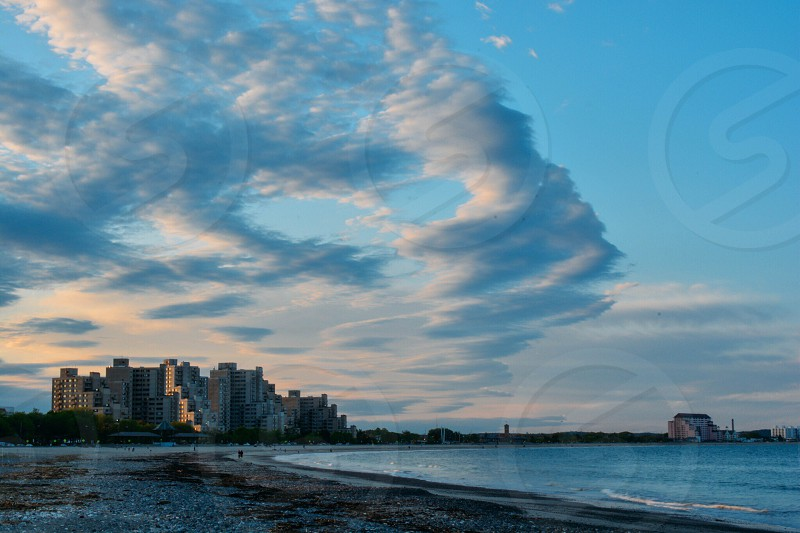 gray buildings near beach and blue skies photo