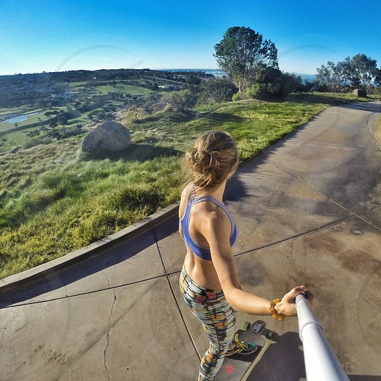 woman wearing blue sports bra and multicolored leggings riding on pintail longboard on empty road under blue sky during daytime photo