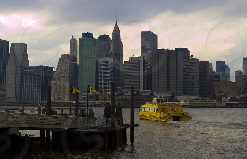 yellow ship sailing towards city photo