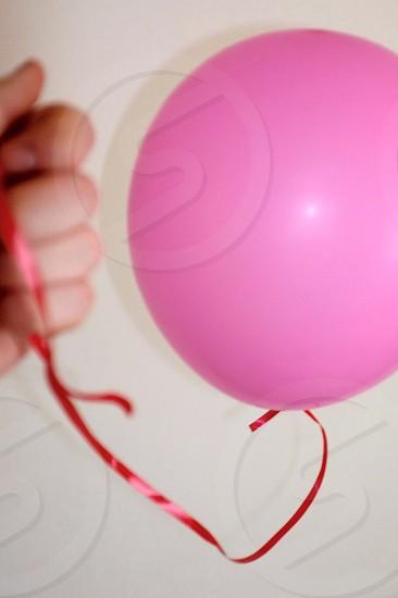 A hand pulls a rather sad deflating ballon towards the camera. photo