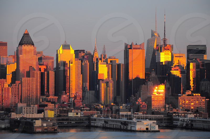 calm body of water with white and brown pier near highrise building with orange reflection by sun rays during sunset photo