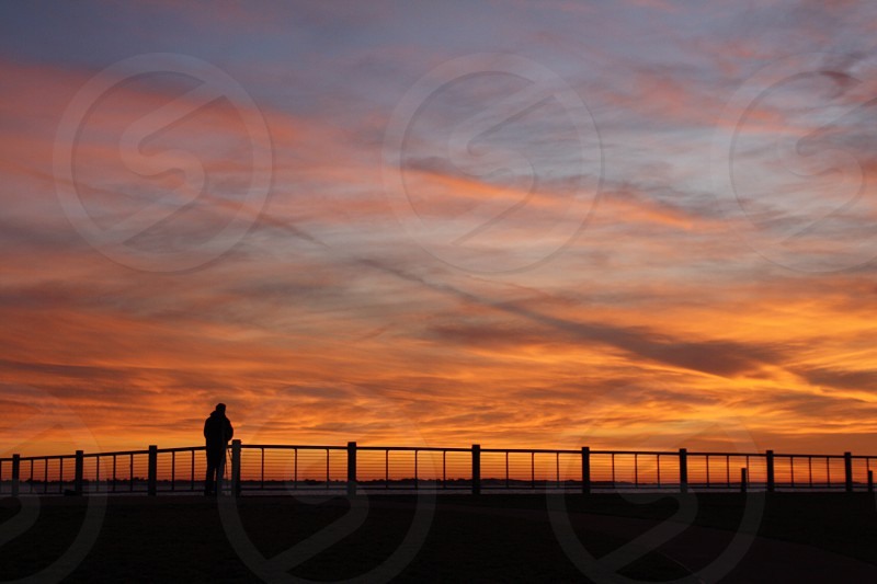 Man standing alone admiring the beautiful sunset.  photo