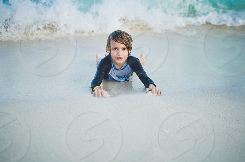 Boy lying in the sand looking at viewer ocean wave coming towards him in the background. photo