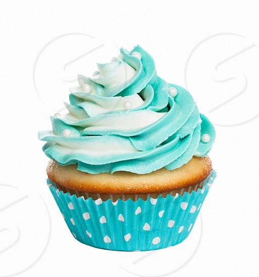 Teal birthday cupcake with buttercream icing isolated on white. photo