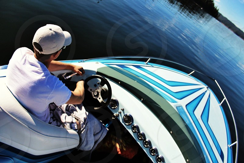 man in white shirt riding speed boat photo