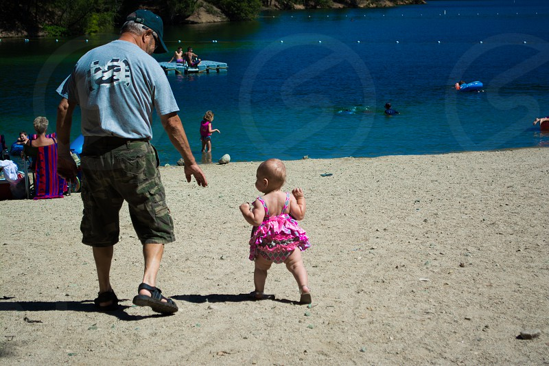 Great Grandpa and Autumn walking to the water together. photo