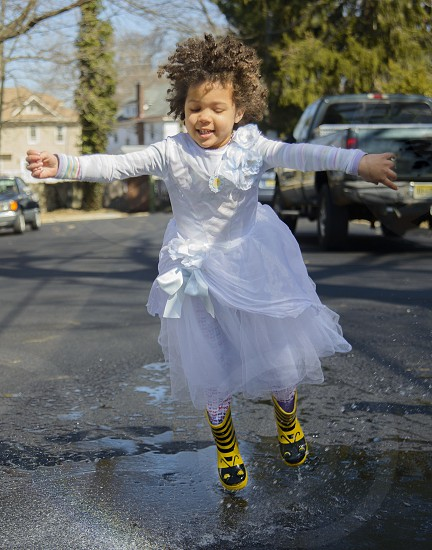 girl in white dress with yellow and black rain boots jumping on water puddles in the street photo