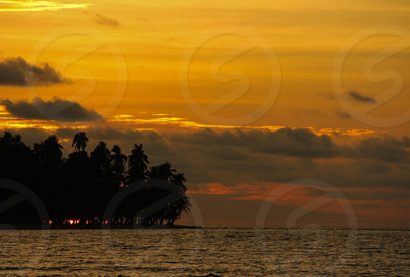 Sun setting on the horizon behind a small palm tree-lined island in the San Blas Islands Panama.  Sunset palm trees photo