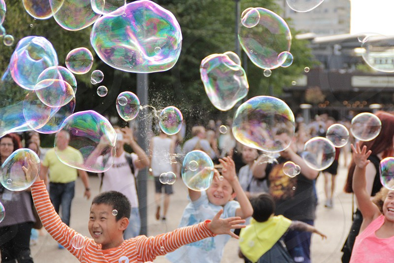 time lapse photo of children playing bubbles photo