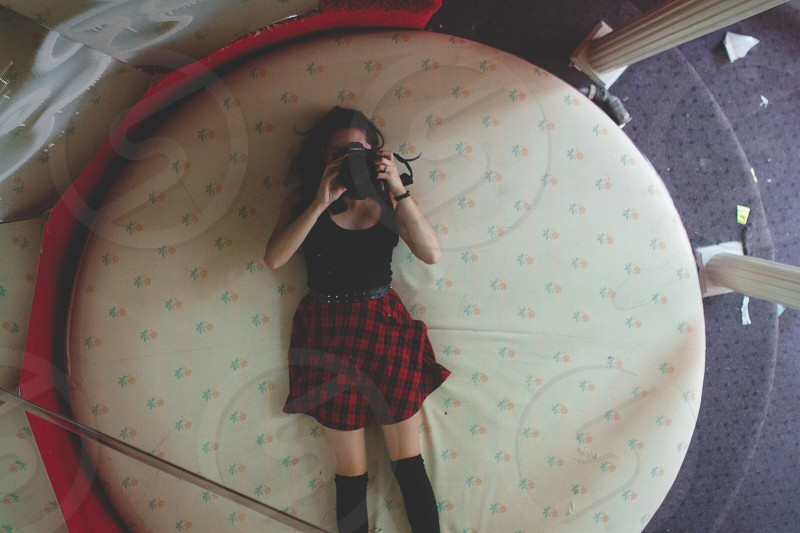 woman wearing black scoop neck shirt red-and-black plaid skirt black thigh-high boots holding DSLR camera lying on bed photo