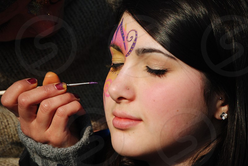 person drawing on girl's face photo