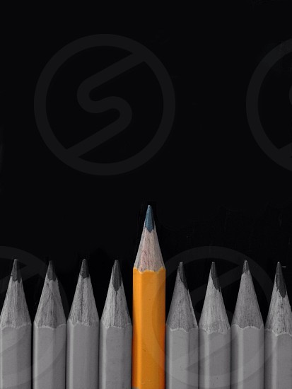8 grey wooden pencils and 1 yellow wooden pencil photo