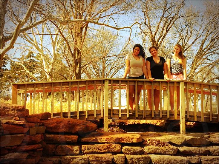 3 women standing on wooden bridge photo