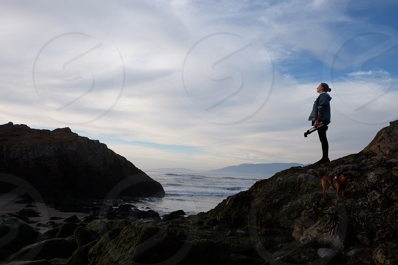 woman standing in rock beside seashore under cloudy sky during daytime photo