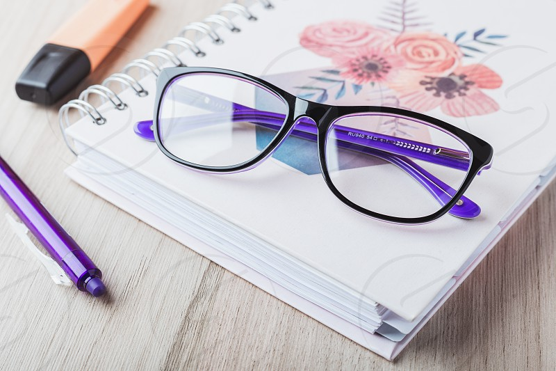Woman glasses with planner and pencils photo