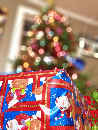 red and blue gift box beside christmass tree with red yellow and green chain lights photo