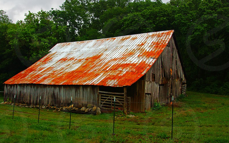 red roofed wood barn behind barbed wire fence photo