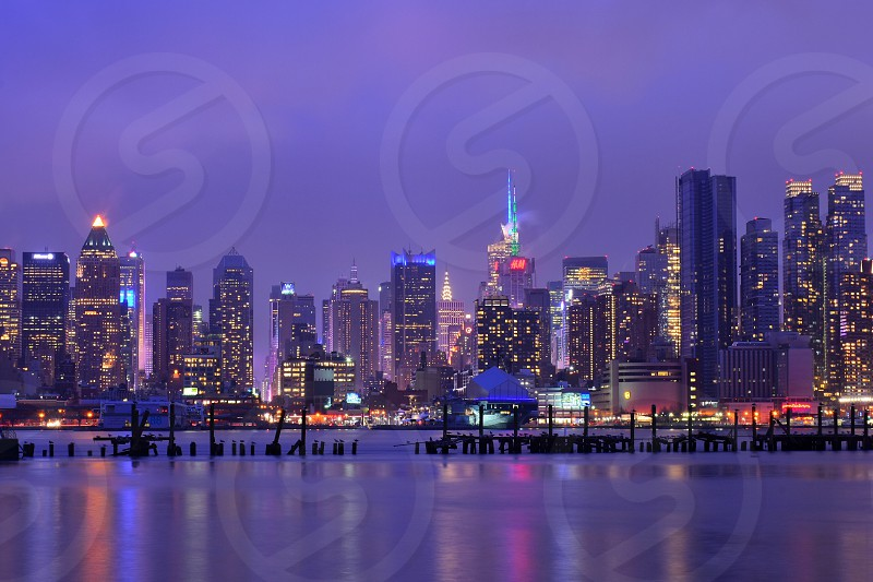 view of cityscape with lighted high rise buildings near body of water at nighttime photo