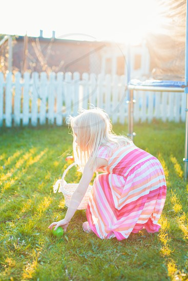 Young girl searching for easter eggs in the backyard photo