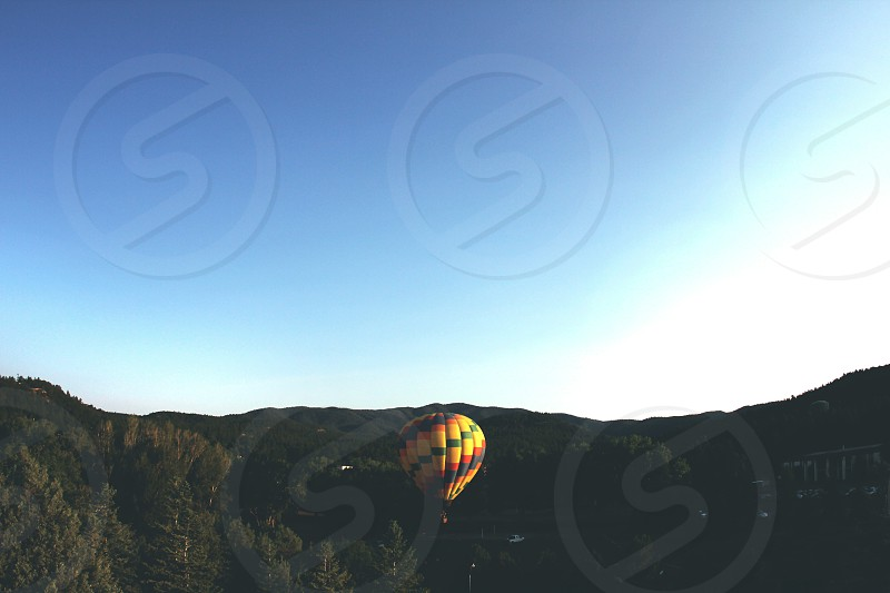 A hot air balloon rises over the mountains as the sun rises to greet it in New Mexico. photo
