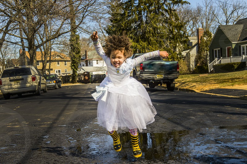 girl in white long sleeve dress wearing yellow and black stripe rain boots jumping off the water puddle photo