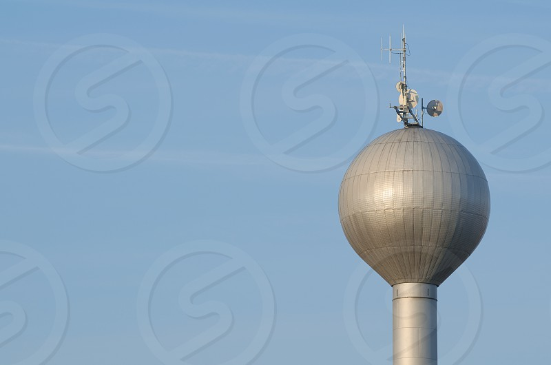 Bright Water Tower with Antenna Under Blue Sky Closeup photo