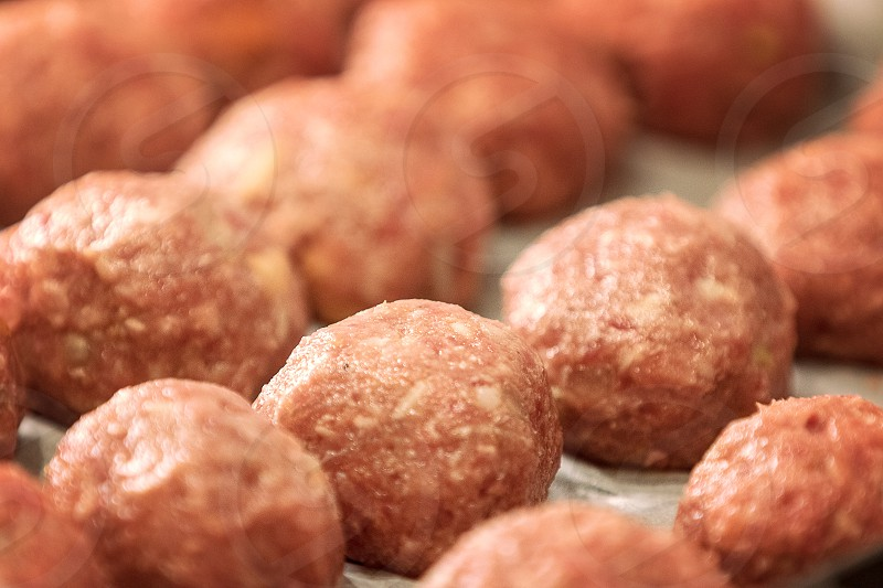 Uncooked dumplings on tray. Fresh minced meat in the form of balls with pepper salt. Artificial meat concept soft focus. photo
