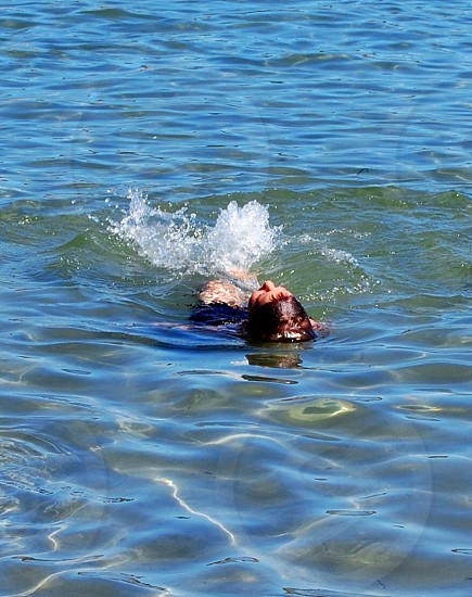 person swimming in the ocean photo